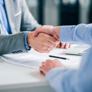 Zwei männliche Personen geben sich die Hand zur Einigung